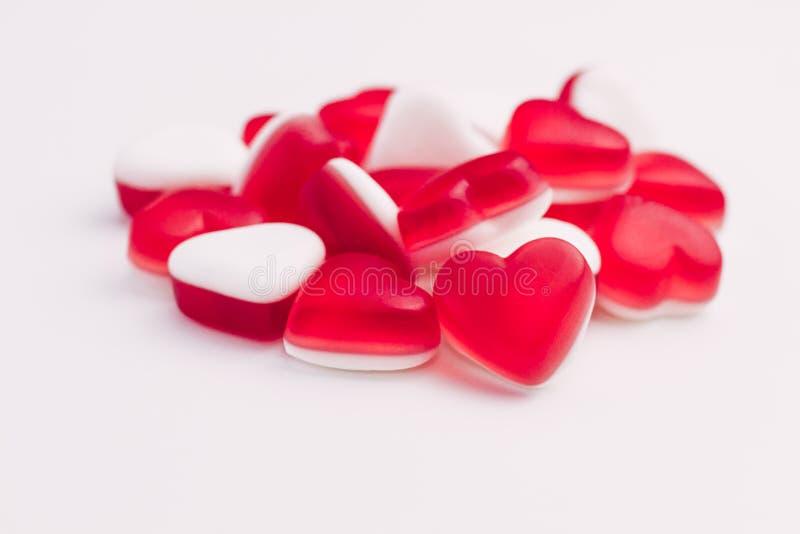 Högen av hjärta formade röda och vita gelésötsaker på vit bakgrund placera text royaltyfri foto
