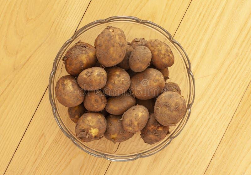 Högen av nya nya rå potatisar med skalar på i en exponeringsglasbunke Slut upp p? tr?bakgrund - Bild royaltyfri foto