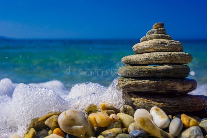 Högen av pyramiden formade kiselstenar Vågor slår stenarna Havs- och strandbakgrund Sommar- och feriebegrepp Izmir Turkiet royaltyfri bild