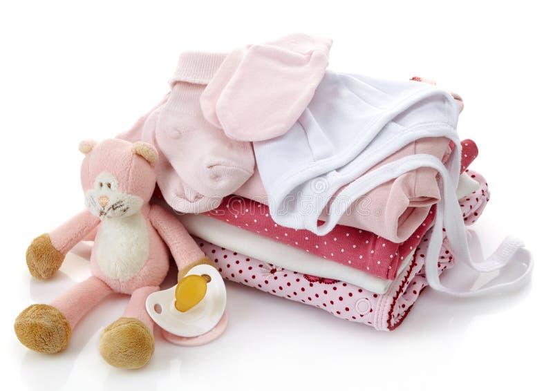 Högen av rosa färger behandla som ett barn kläder arkivfoton