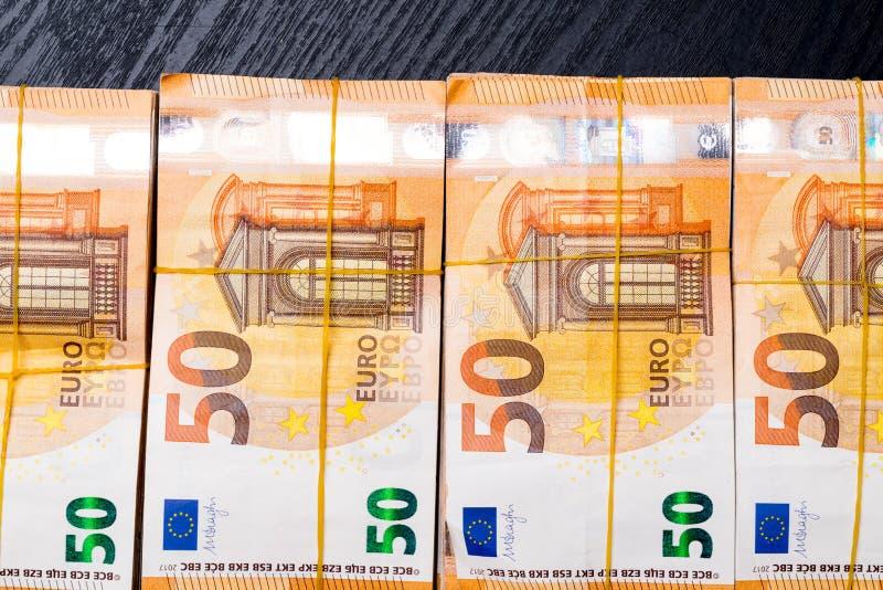 Högen av verkligt euro 50 noterar 50 eurosedlar under gummibandet som isoleras på svart Omkring 20000 euro värde royaltyfri foto