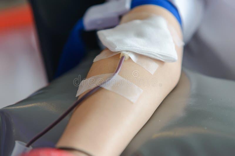 Höger arm av den asiatiska mannen som mottar blod och rymmer gummibollen i hand Sjukvård och välgörenhet Transfusionbloddonation royaltyfri bild