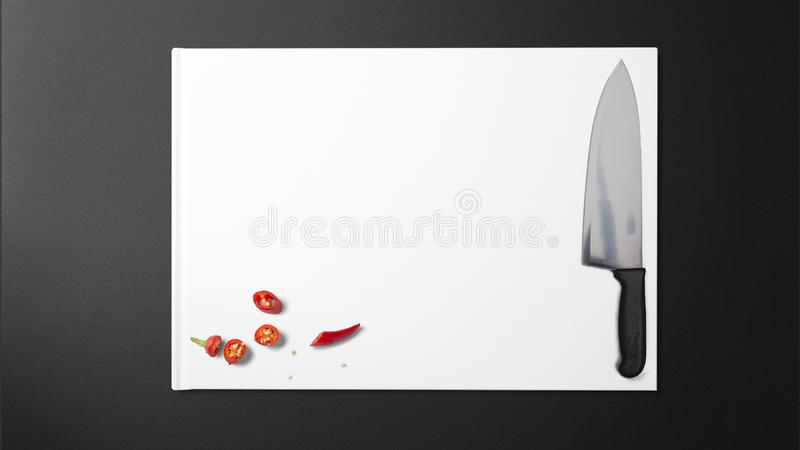 Högg av chilies med den skarpa kniven på vitbok på svart bakgrund i köket arkivbild
