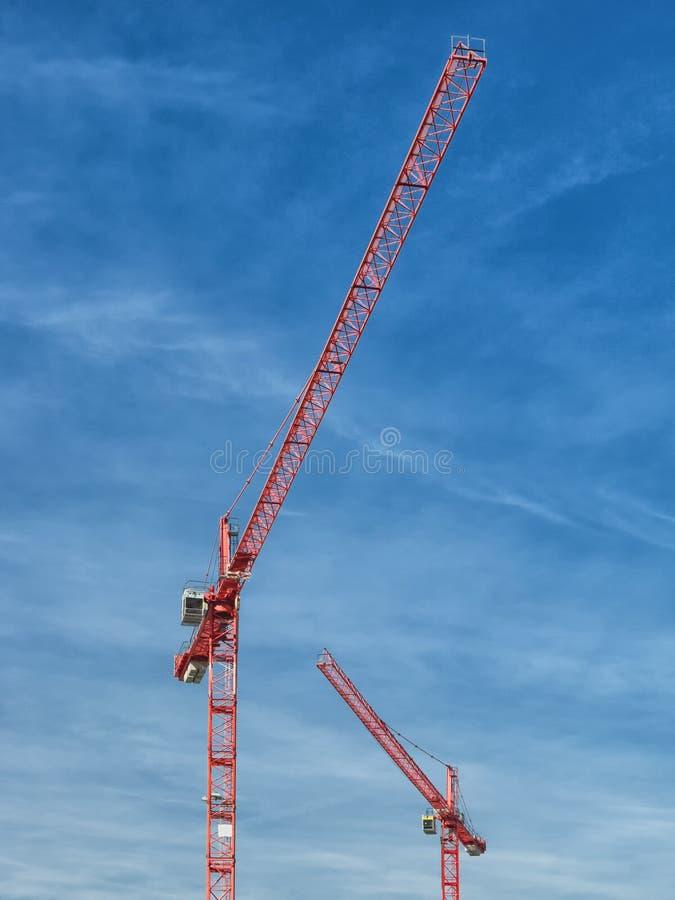 Höghus kran, blå himmel, vita moln i ljuset av inställningssolen arkivbild