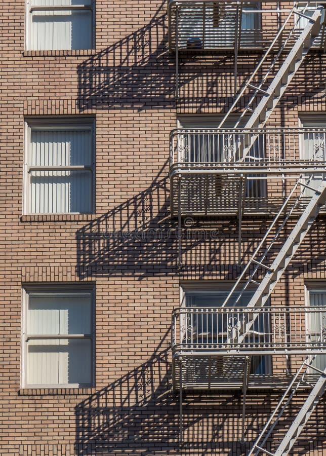 Höghustegelstenbyggnad med stegen för brandflykt royaltyfria foton