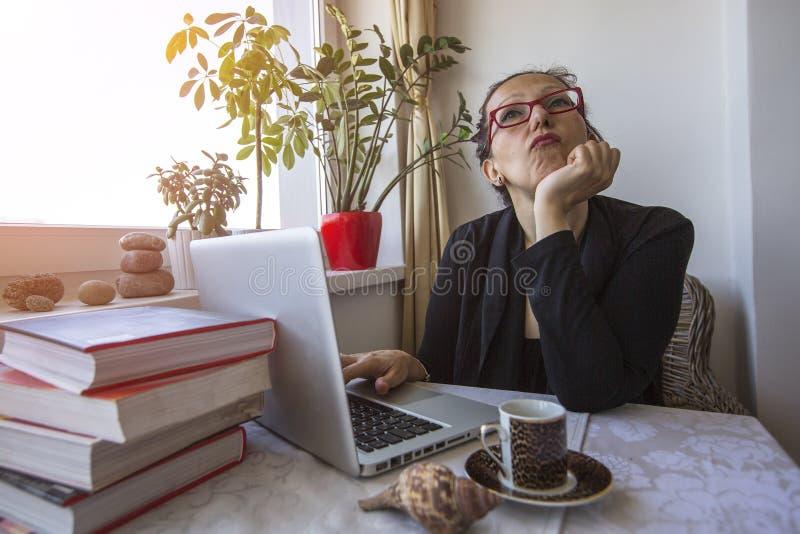 Högmodigt arrogant kvinnasammanträde i kontoret med en bärbar dator arkivbild