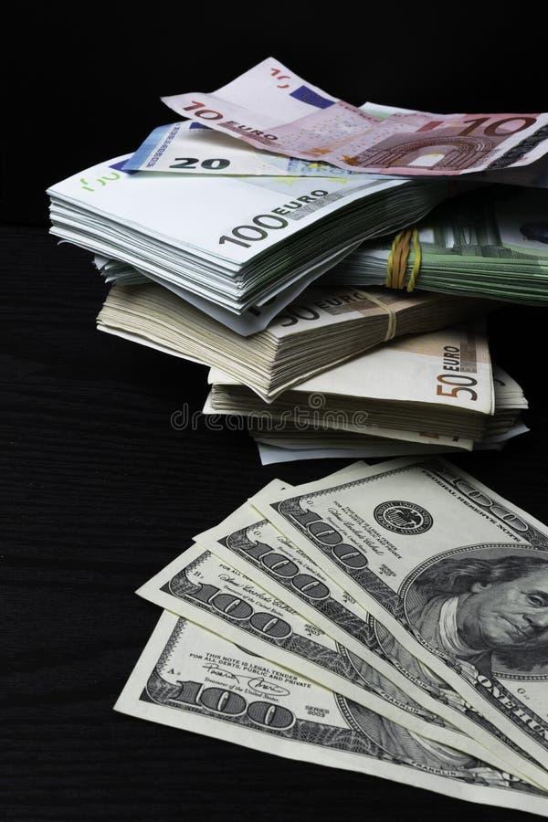 Högpengar: dollar och eurosedlar på skrivbordet arkivbild