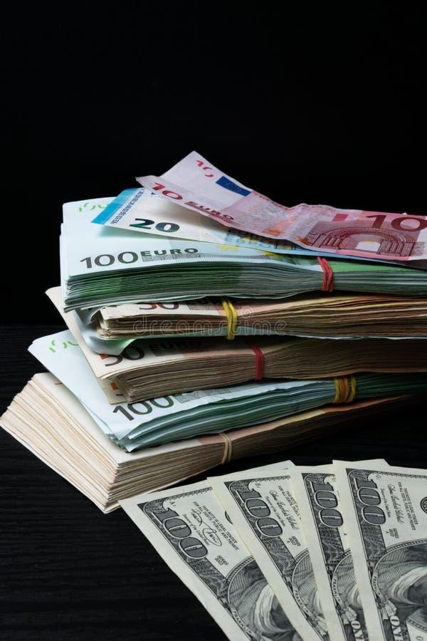 Högpengar: dollar och eurosedlar på skrivbordet royaltyfri fotografi