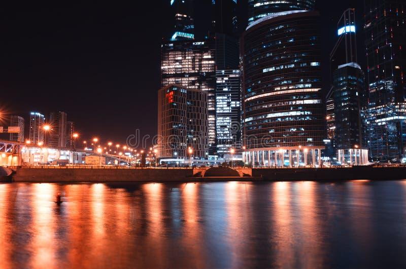 Högra alighned Moskvastadsbyggnader på bakgrunden för nattflodbank royaltyfri bild