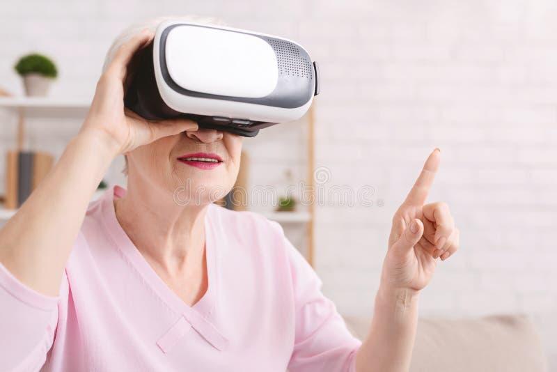 Högre kvinna i VR-headset som trycker på virtuell knapp arkivfoton