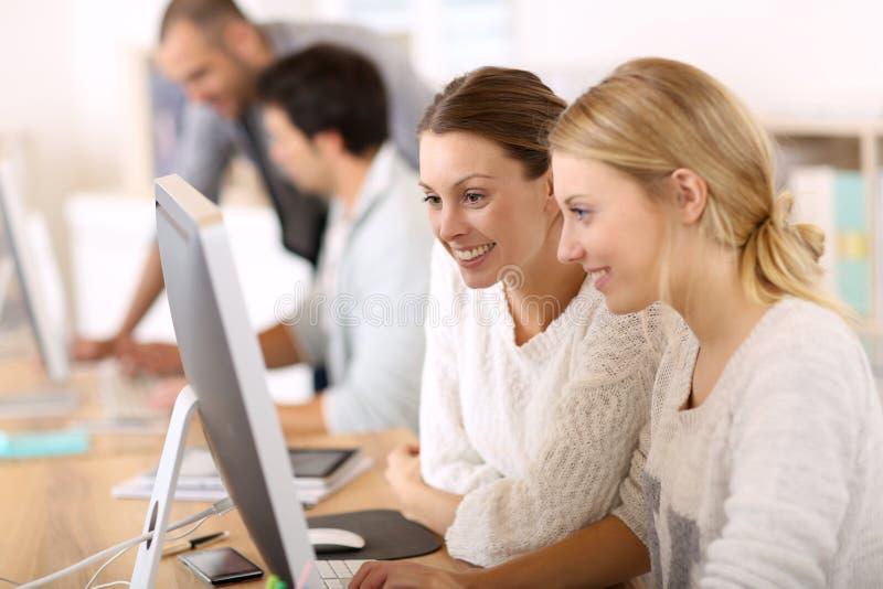 Högskolafolk som arbetar på datorer i grupper royaltyfria bilder