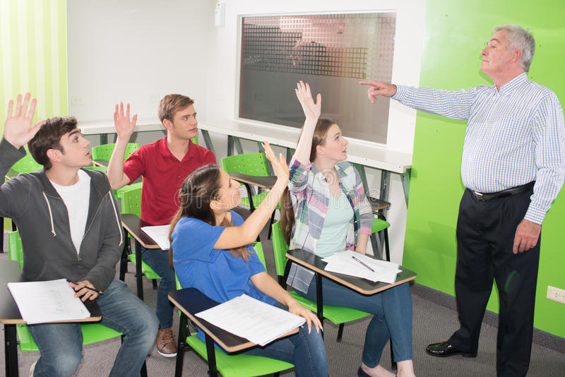 Högskolaläraren hjälper hans studenter arkivfoto