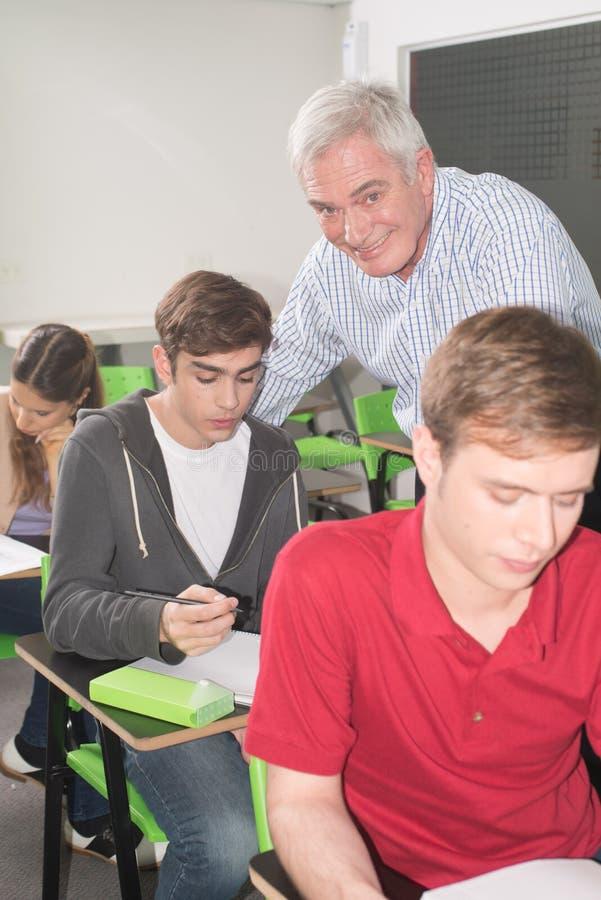 Högskolaläraren hjälper hans studenter royaltyfri foto