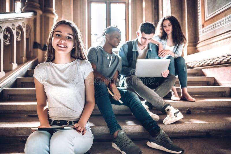 Högskolaliv Ett härligt ungt studentsammanträde på trappa i universitetsområde genom att använda minnestavlan, medan hennes vänne royaltyfri fotografi