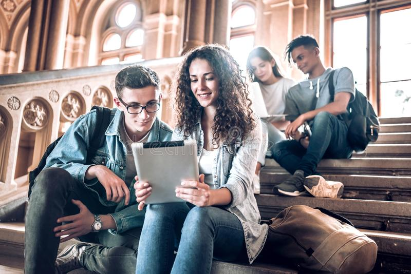 Högskolaliv Grupp av studenter som använder en minnestavla, medan sitta på trappa i universitet royaltyfria bilder