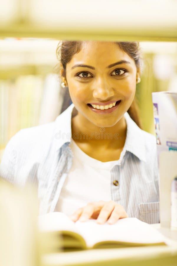 Högskolestudent bak bokhyllan fotografering för bildbyråer