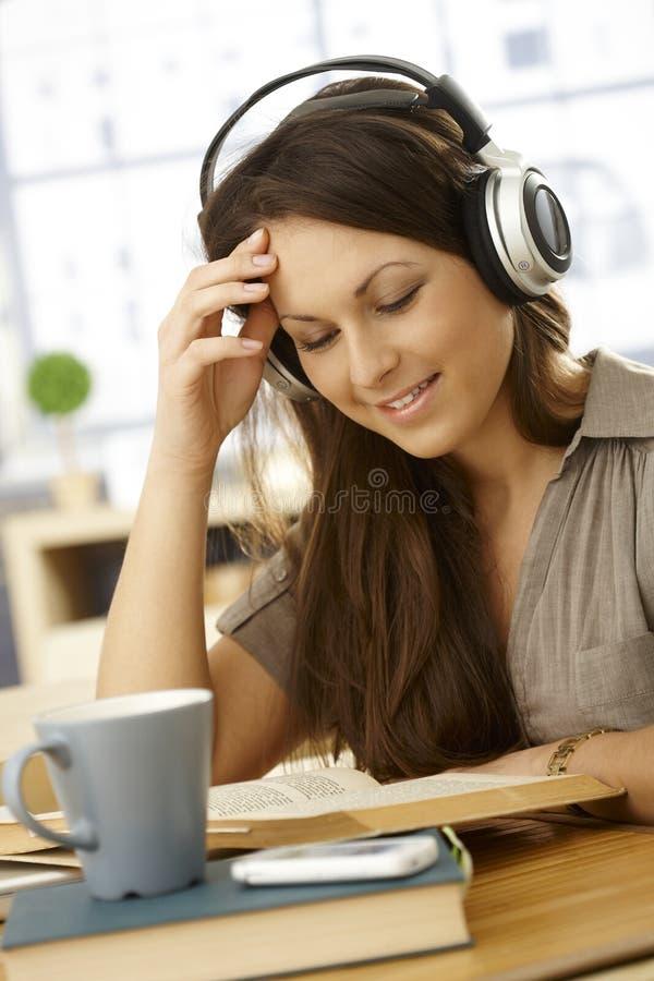 Högskolestudent som hemma lär med hörlurar arkivfoton