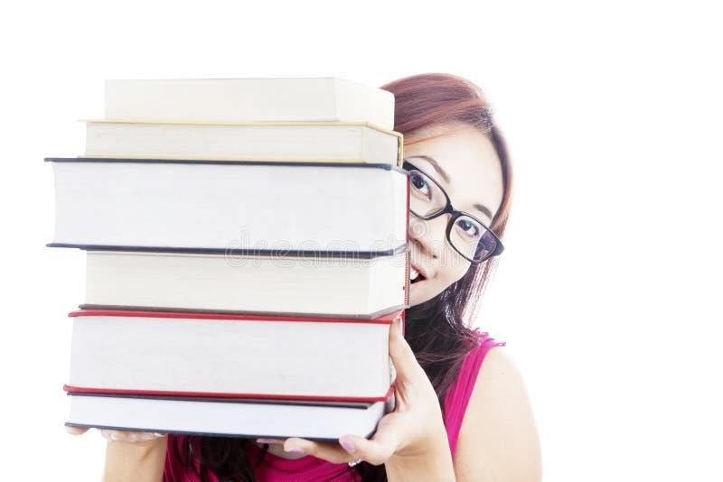 Högskolestudent som ler bak böcker royaltyfria foton