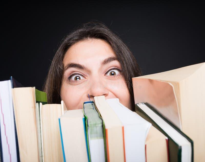 Högskolestudent som omges av böcker royaltyfria bilder