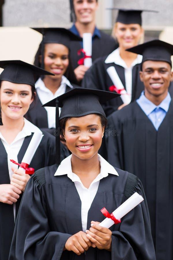 Högskolestudentavläggande av examen arkivfoton