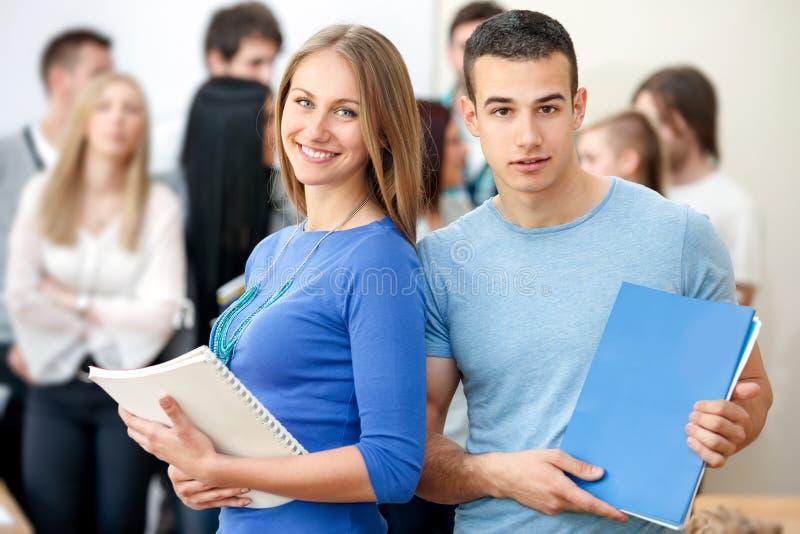 Högskolestudenter med böcker arkivbild