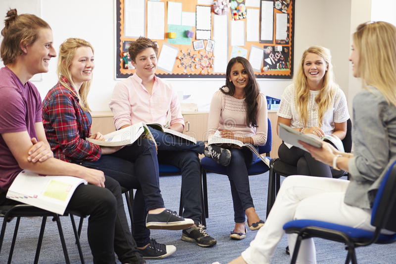 Högskolestudenter med handleder Having Discussion royaltyfria foton