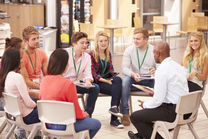 Högskolestudenter med handleder Having Discussion fotografering för bildbyråer