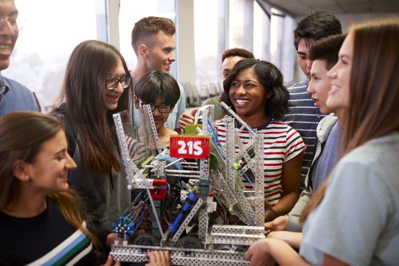 Högskolestudenter med lärareHolding Machine In vetenskap eller robotteknikgrupp arkivfoton