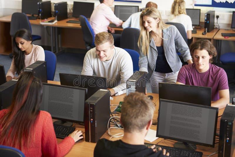 Högskolestudenter på datorer i teknologigrupp royaltyfria bilder