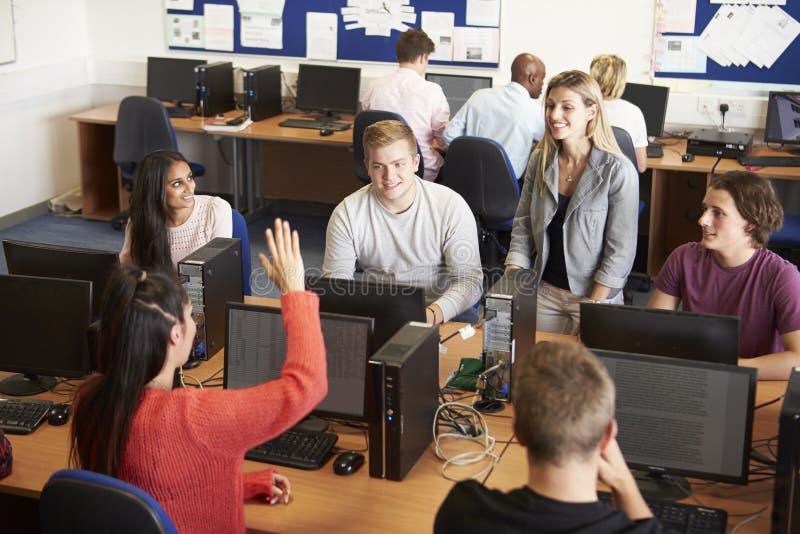 Högskolestudenter på datorer i teknologigrupp royaltyfri bild