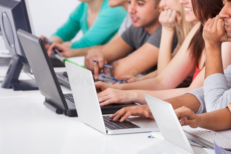 Högskolestudenter som använder bärbara datorer royaltyfria bilder