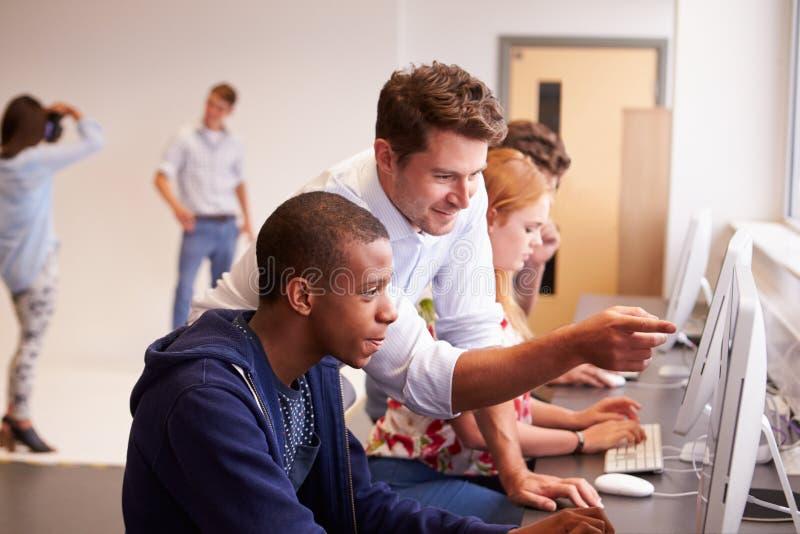 Högskolestudenter som använder datorer på massmediastudiekurs arkivfoton