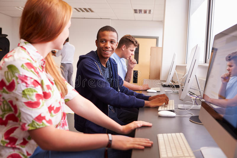 Högskolestudenter som använder datorer på massmediastudiekurs royaltyfria bilder