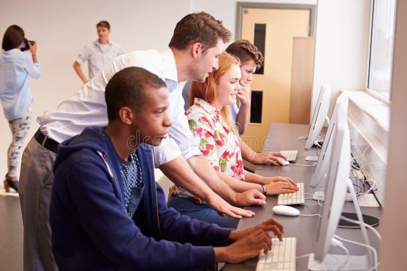 Högskolestudenter som använder datorer på massmediastudiekurs royaltyfria foton