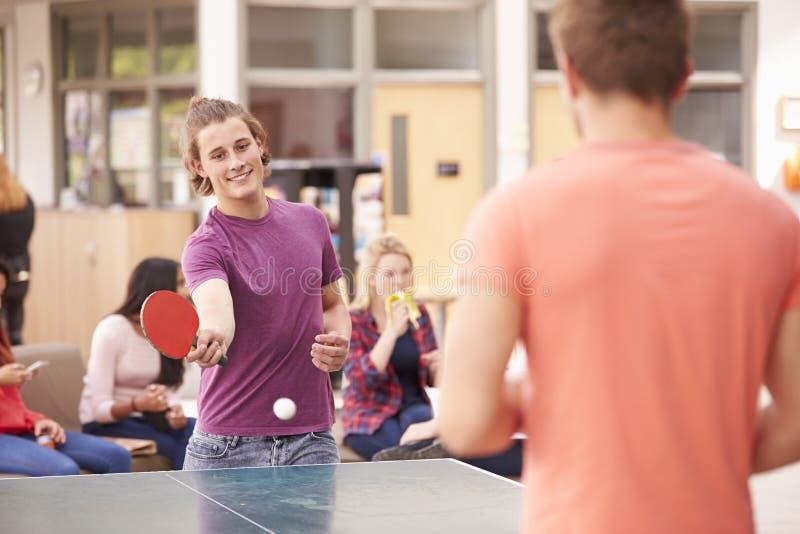 Högskolestudenter som kopplar av och spelar bordtennis royaltyfri bild
