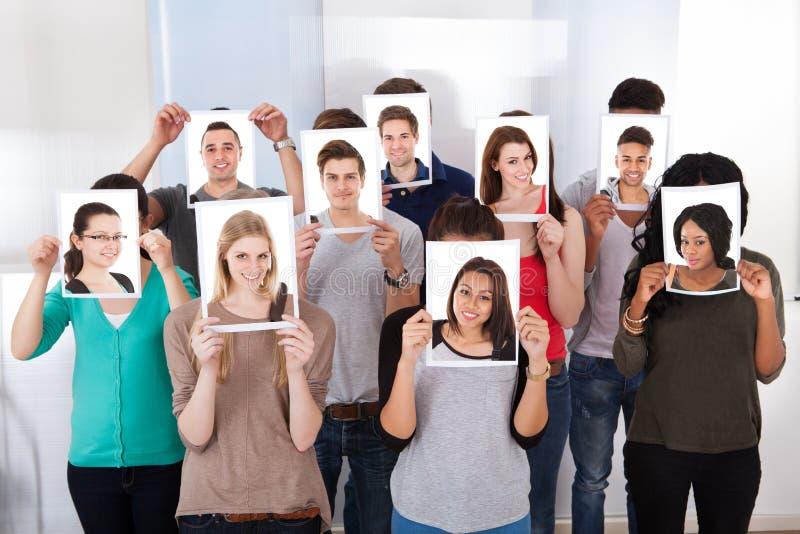 Högskolestudenter som rymmer fotografier främsta av framsidor royaltyfri bild