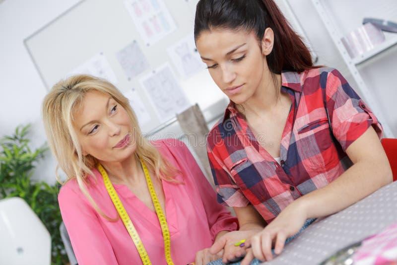 Högskolestudenter som studerar mode och design arkivbilder