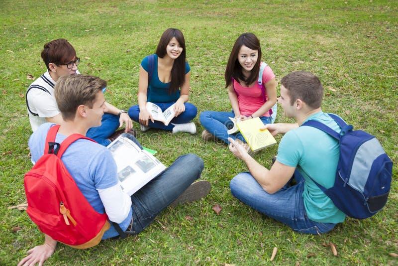 Högskolestudenter som studerar och, diskuterar tillsammans i universitetsområde royaltyfri bild