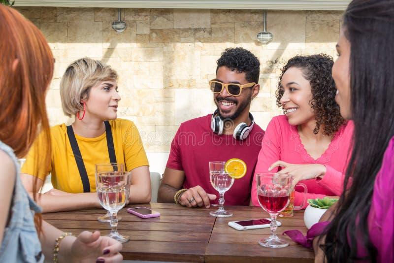 Högskolestudenter som tillsammans festar på den utomhus- kaféstången Vår, arkivbild
