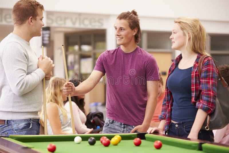 Högskolestudenter som tillsammans kopplar av och spelar pölen royaltyfria foton