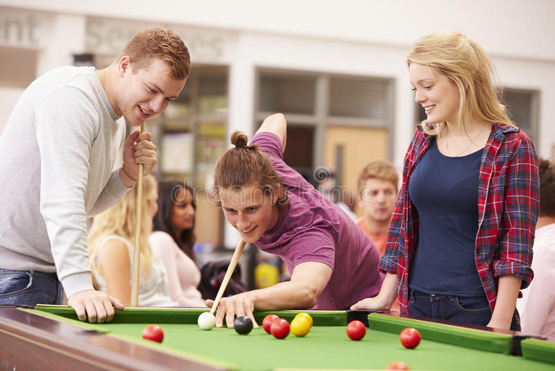 Högskolestudenter som tillsammans kopplar av och spelar pölen royaltyfri bild