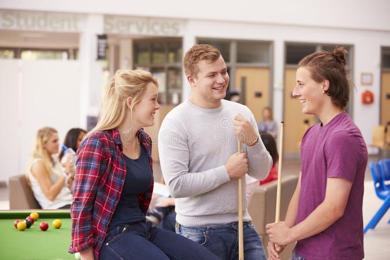 Högskolestudenter som tillsammans kopplar av och spelar pölen royaltyfri fotografi