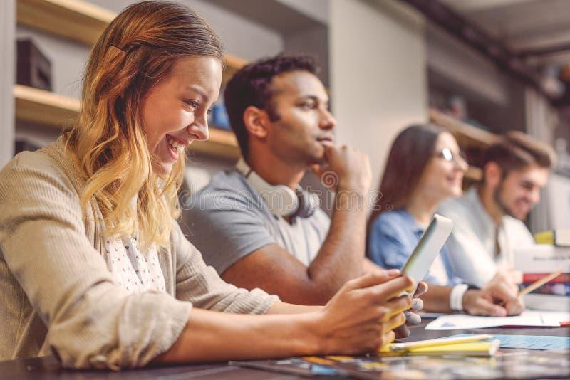 Högskolestudenter som tillsammans sitter och studerar arkivfoton