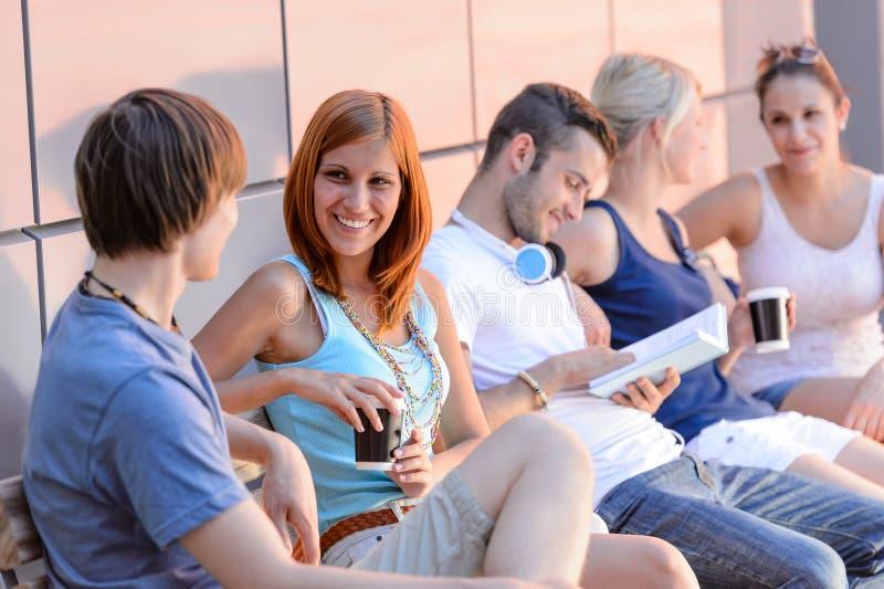 Högskolestudenter som utanför sitter vid den moderna väggen royaltyfria bilder
