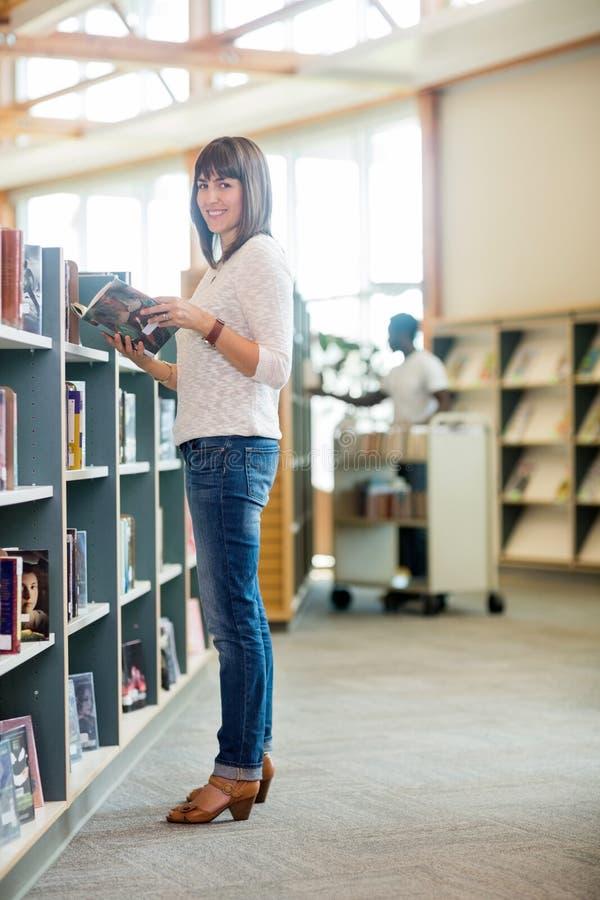 HögskolestudentHolding Book In bokhandel royaltyfria bilder