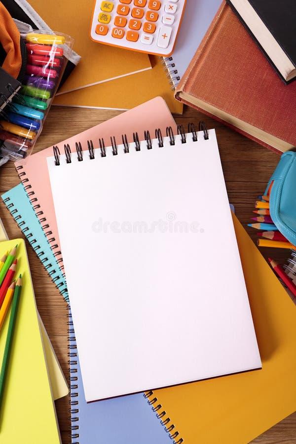 Högskolestudentskrivbord med den tomma handstilboken, vitt kopieringsutrymme arkivbilder