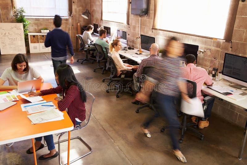 Högstämd sikt av arbetare i upptaget kontor för modern design arkivbilder