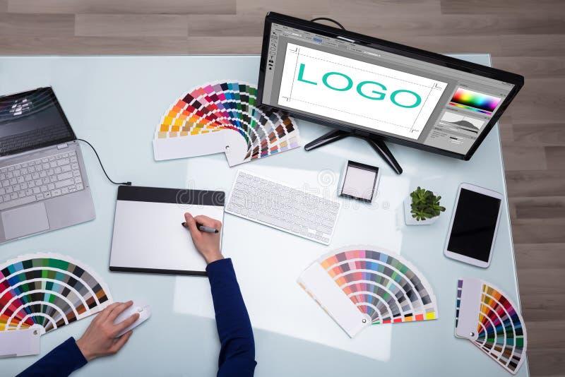 Högstämd sikt av den märkes- handen för ` som s arbetar på datoren royaltyfri bild