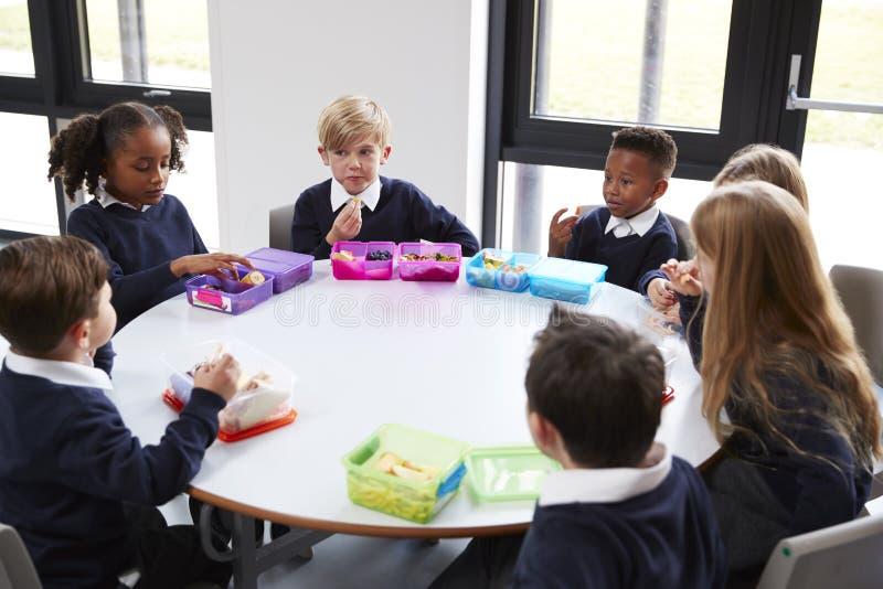 Högstämd sikt av grundskola för barn mellan 5 och 11 årungar som tillsammans sitter på en rund tabell som äter deras matsäckar arkivbilder