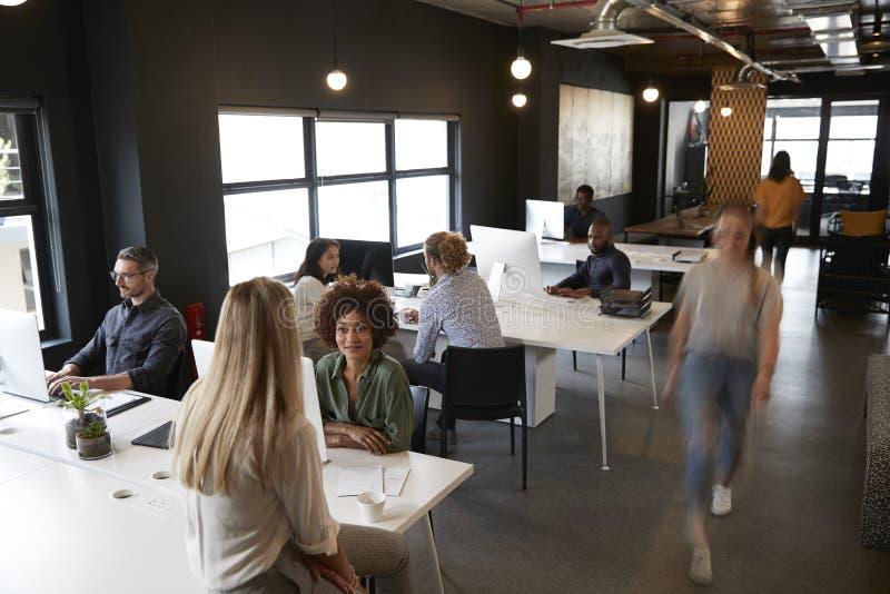 Högstämd sikt av idérika affärskollegor som arbetar på skrivbord och går till och med ett upptaget kontor arkivbilder